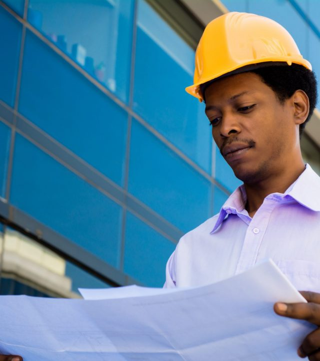 Portrait of professional architect in helmet looking at blue prints outside modern building. Engineer and architect concept.